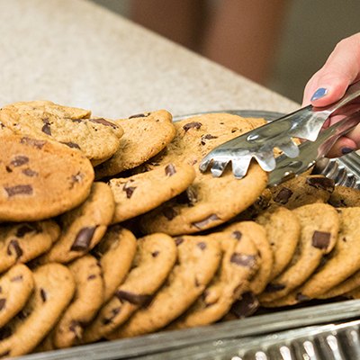 a woman's hand holding tongs selecting a chocolate chip cookie