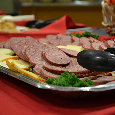 a close shot of a party tray with tongs, cheese, and meat sliced on it