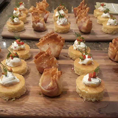 a variety of bite-sized hors d'oeuvres on a wooden platter