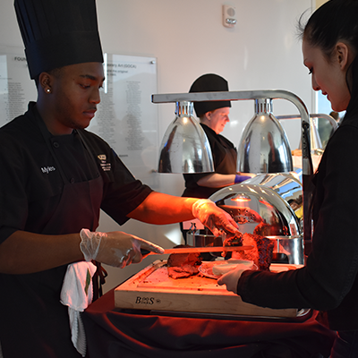 a cook serving meat from a buffet to a patron